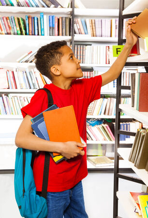 Schoolboy with blue bag puts hand on bookshelf and holds colorful books in library photo