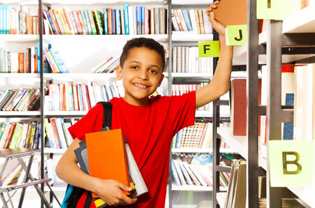 Cute boy with hand on bookshelf and holds colorful books in library photo