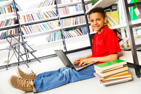 Smiling boy with pile of books sitting on floor in library and typing on laptop photo