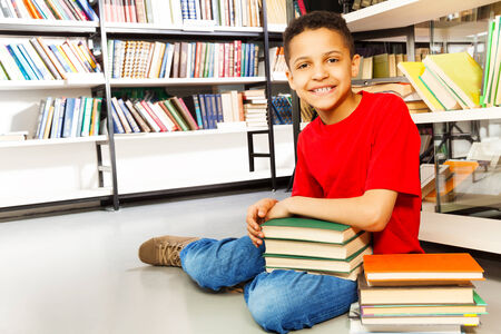 Smiling schoolchild with pile of books sitting on floor in library photo