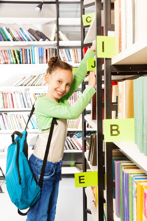 schoolkid search: Colegiala con el bolso azul de la b�squeda de libros y con libros de ejercicios en la estanter�a de la biblioteca