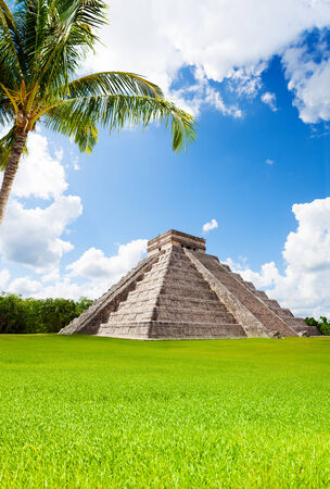 Monument of Chichen Itza in summer, green grass and palm in Mexico photo