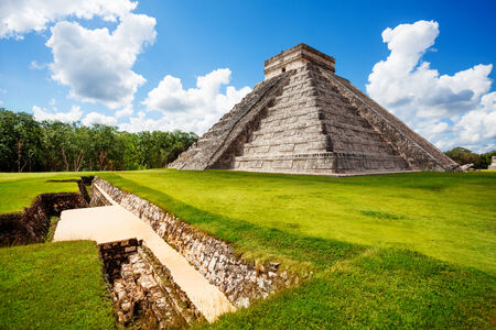 mexico culture: Monument of Chichen Itza on the green grass during summer in Mexico