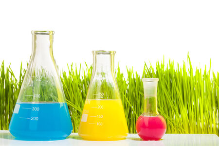 Colorful liquids in three different of size test tubes standing in a row according to the height on the background with green grass