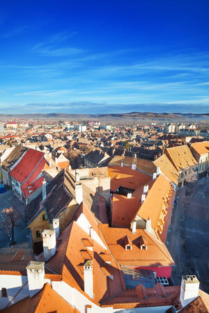 Rows of red roofs and horizon with blue sky in beautiful Sibiu, Romania photo