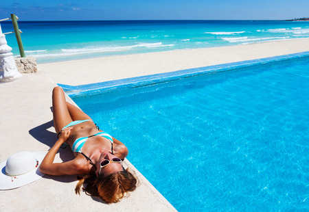 Girl with sunglasses sun bathing near swimming pool and blue ocean on the horizon
