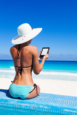 Beautiful woman from back with white hat reads kindle photo