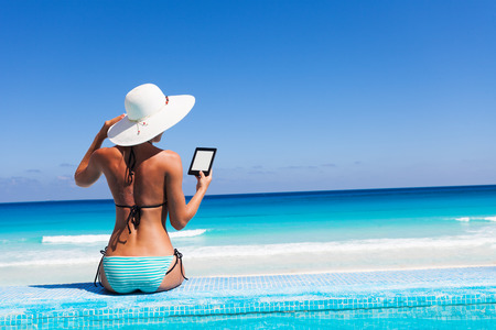 resort beach: Beautiful woman from back with white hat reads kindle and holds a hat