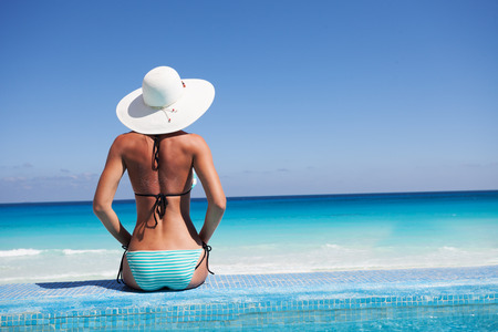 Silueta de la mujer joven en la playa con el sombrero blanco de la parte posterior