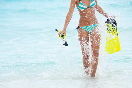 hot girl legs: Beautiful female body with yellow fins and snorkeling mask on sea background