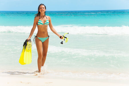 stripped: Smiling girl wearing striped swimsuit with fins and mask walking on coast Stock Photo