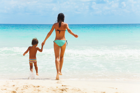 child model: Small child and young woman together running to the sea holding hands from the back