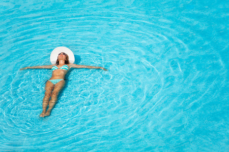 women in bikini: Girl with white hat swimming in crystal-clear blue swimming pool Stock Photo