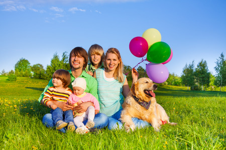 Smiling positive family sitting on grass with balloons and dog photo