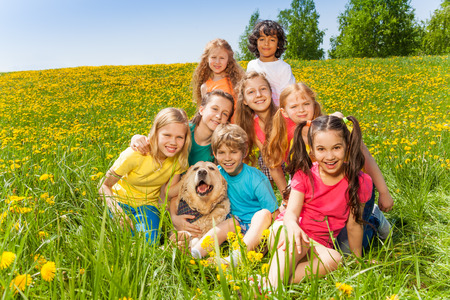 Cheerful kids with dog sitting on the green  grass in summer photo