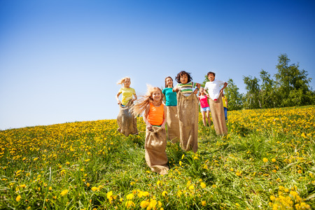 Children jump in sacks while playing together in field with dandelions photo