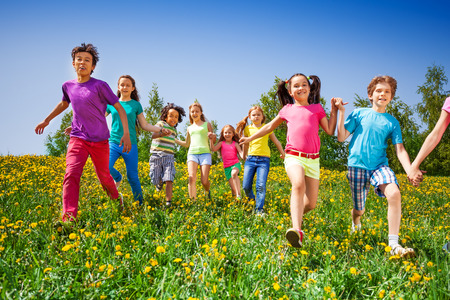 Happy kids run and hold hands in green meadow during summer photo
