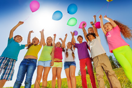 Children standing in semi-circle with arms up to flying balloons in green field