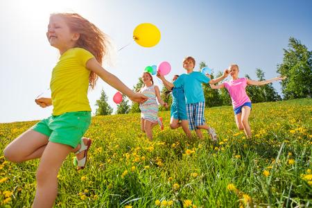 spielen: Aufgeregte Kinder mit Luftballons in der grünen Wiese im Sommer laufen