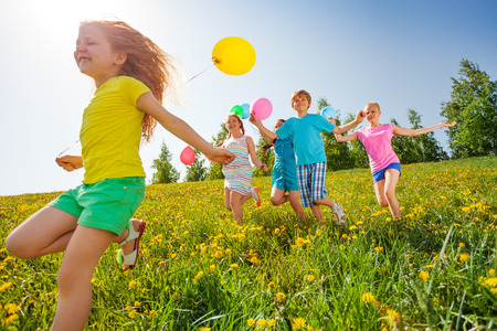 Excited kids with balloons run in green field in summer Stock Photo
