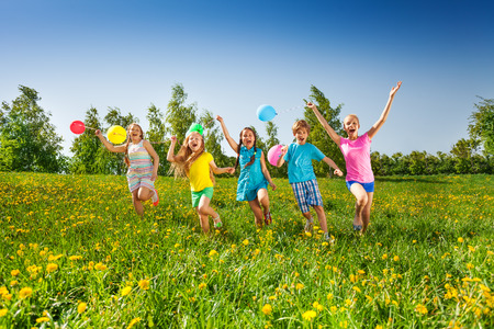 green meadows: Happy excited five children with balloons running in green field with yellow flowers in summer Stock Photo