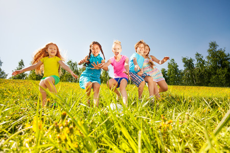 Happy children playing football in yellow meadow in summer