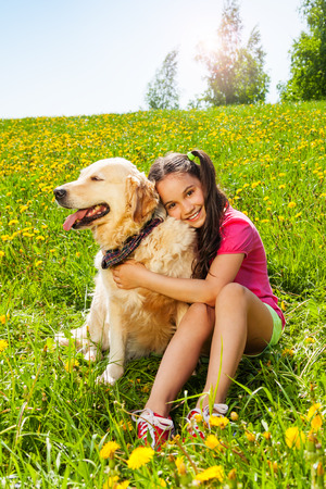Smiling girl hugging cute dog sitting on the grass in summer photo