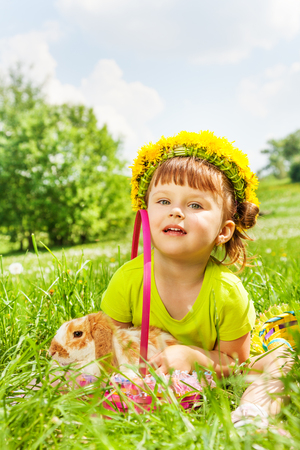 Happy girl with flowers circlet with rabbit in the basket sitting in the park in summer