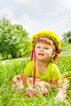 circlet: Ragazza felice con i fiori cerchietto con coniglio nel carrello seduto nel parco in estate Archivio Fotografico