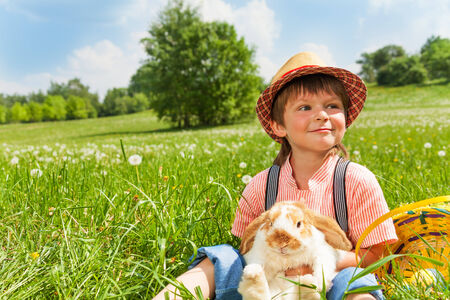 Positive boy wearing hat, looking to the right and hugging rabbit in green park photo