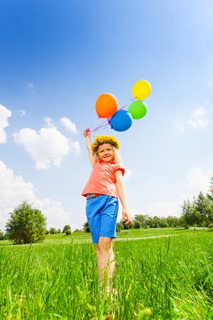 circlet: Piccola ragazza con palloncini colorati che portano cerchietto in estate