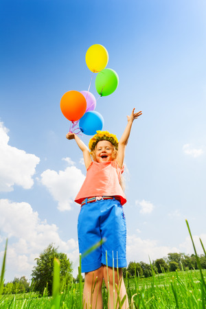 circlet: Happy girl with balloons wearing flower circlet standing in the park