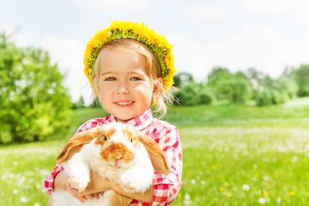 Happy blond girl with yellow flowers circlet with rabbit in the park in summer photo
