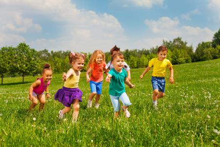 niños jugando en el parque: Jugar a cabritos felices en campo verde durante el verano Foto de archivo