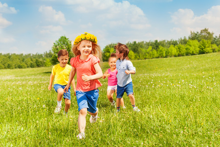 Happy running kids in green field in summer play together Stock Photo