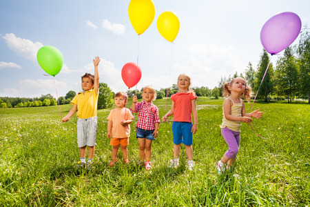 hands high: Five cute children with balloons in green field during summer time