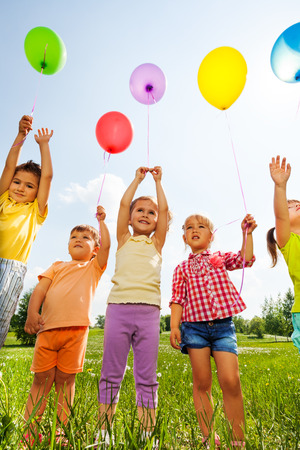 beautiful boys: Funny kids with balloons in the air in green field Stock Photo
