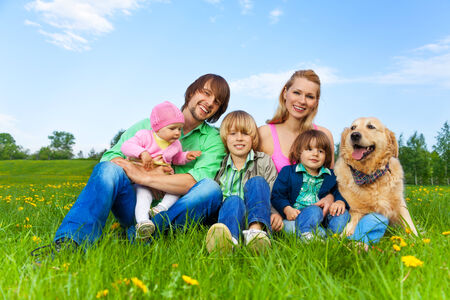 Smiling family sitting on green grass in park with dog in summer photo