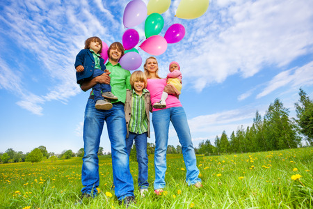 multiple family: Happy family stands with balloons in park in summer