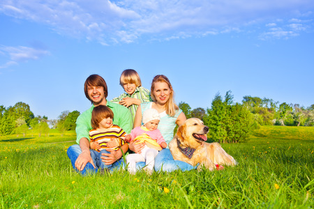 Family sitting on green grass in park with dog in summer photo