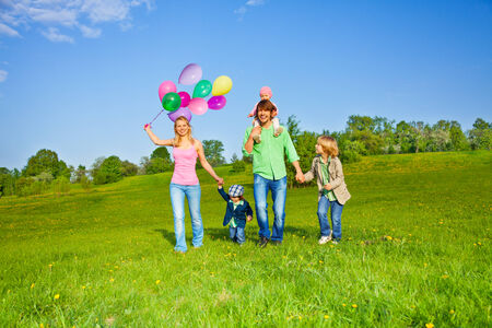 Happy family walks with balloons in park in summer photo