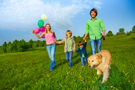 multiple family: Happy family walks with balloons and dog in park in summer
