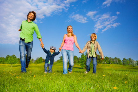 Cheerful parents holding hands and walking with boys in park in summer photo