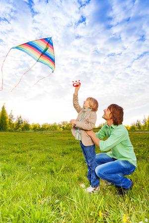 papalote: El padre detiene al ni�o mientras ve la cometa volando en el aire en el parque en verano