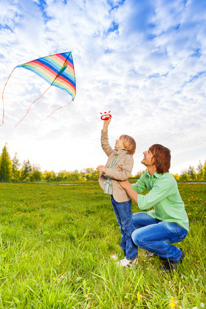 kite flying: Father holds kid while watching flying kite in the air in park in summer