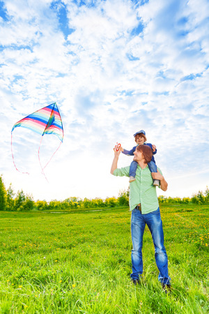Smiling father holds kid on his shoulders with flying kite in the air photo