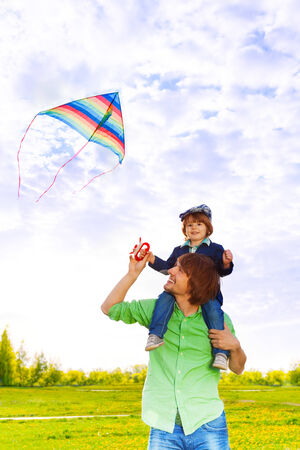 Father holds kid on his shoulders with flying kite in the air photo