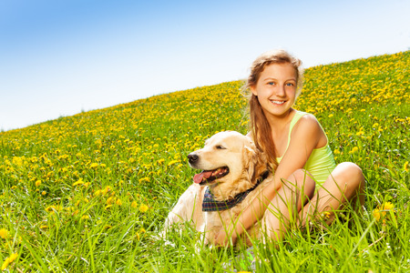 Cute happy girl cuddling dog sitting on the grass in summer