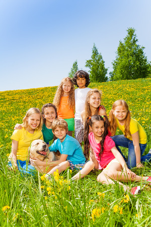 Happy children with dog together in meadow with dandelions in summer photo