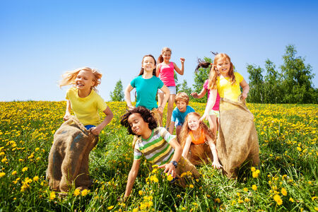 Cheerful children jumping in sacks playing together in summer photo